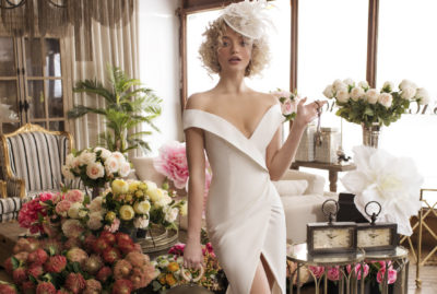 Crepe off shoulder bridal gown with a deep slit and a luxurious train.