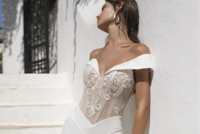 Roxanne is an off shoulder crepe bridal gown with decadent lace and detailing.
