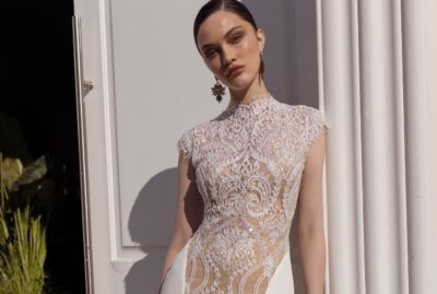 high neckline glamorous detailed wedding gown with crepe material on the sides of the gown. Gown hugs the hour glass figure of the bride
